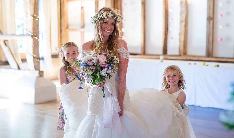 Bride in her white wedding dress with a pastel coloured bouquet