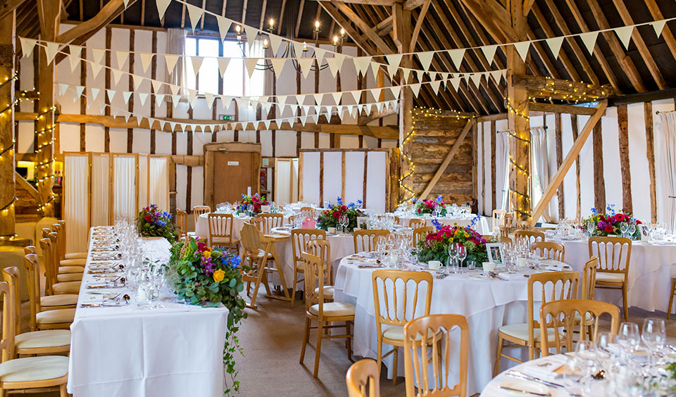 Clock Barn is set up for the wedding reception with tables decorated with gorgeous summer wedding flowers