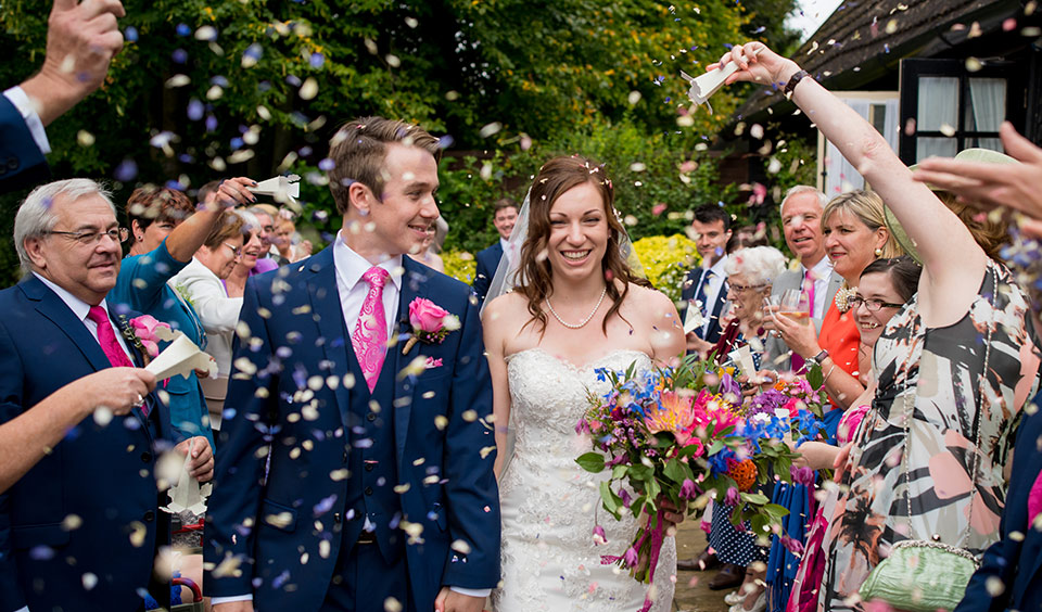The happy newlyweds leave the wedding barn as guests throw wedding confetti – wedding venues Hampshire