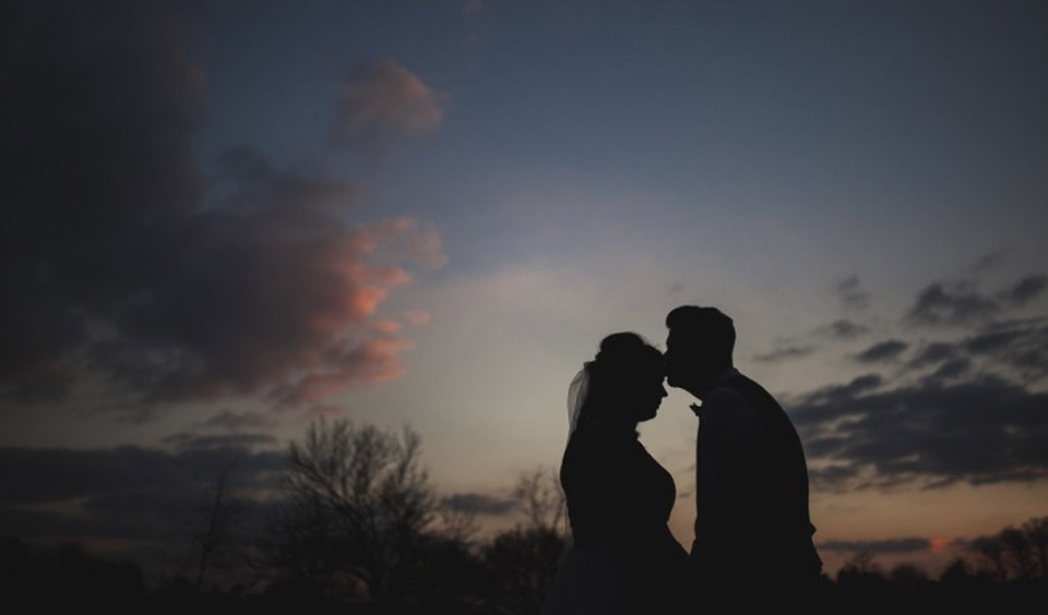 The happy couple kiss as the sun goes down on this stunning wedding venue in Hampshire