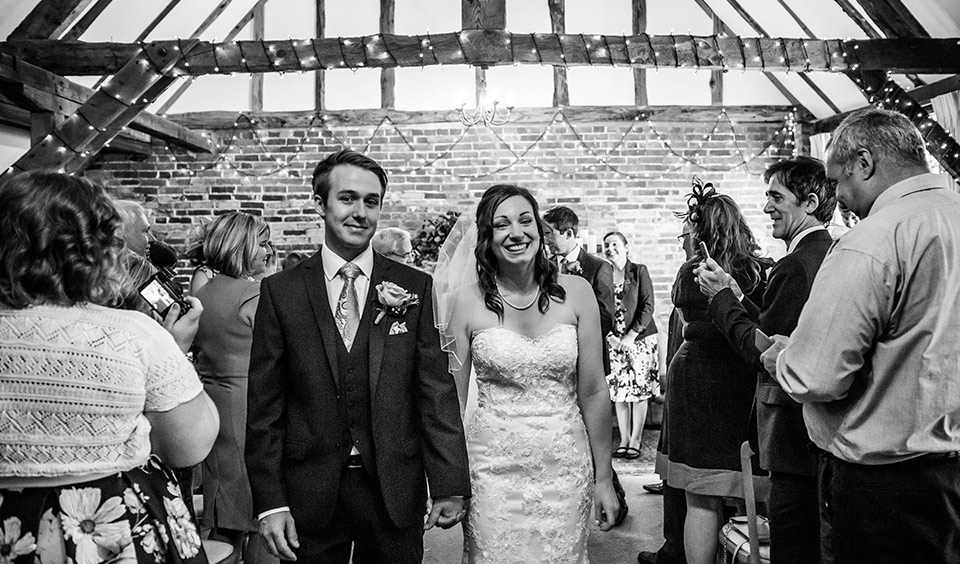 The happy bride and groom leave the wedding ceremony barn after exchanging marriage vows
