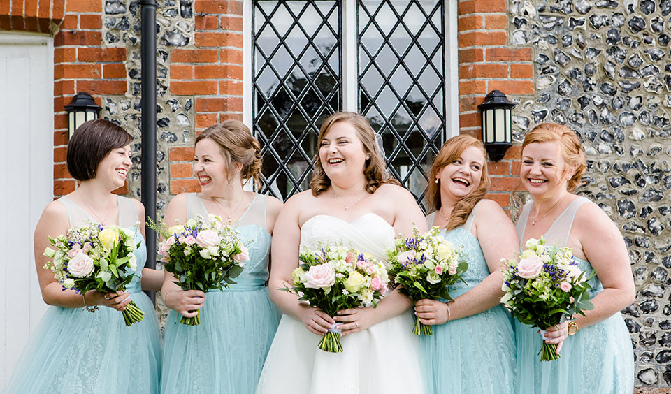 The bride stands with her bridesmaids who all wore pale blue bridesmaid dresses