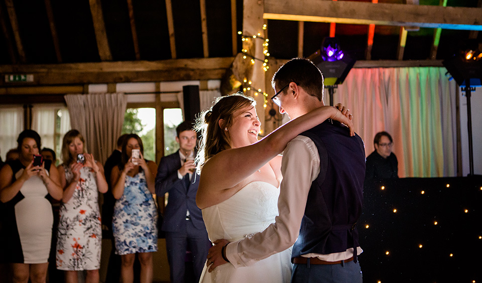 The bride and groom enjoy their first wedding dance as newlyweds in front of wedding guests
