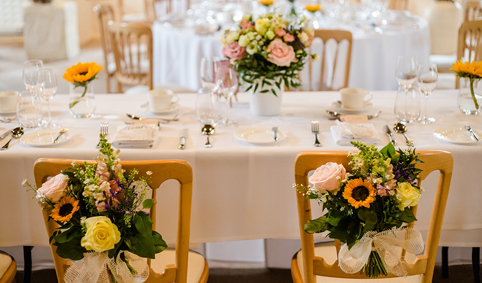 Wedding flowers decorated the tables and chairs in the main barn suiting the couple's summer wedding theme