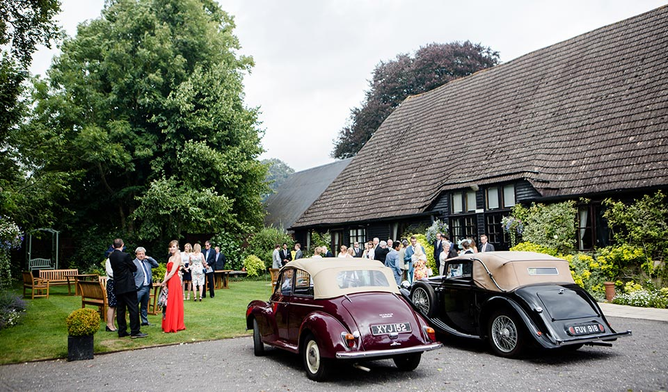 Two stunning vintage wedding cars are parked outside of the beautiful country barn wedding venue