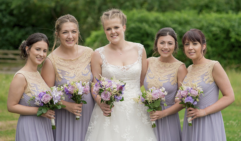 The bride stands with her bridesmaids who were lavender bridesmaid dresses each holding flowers