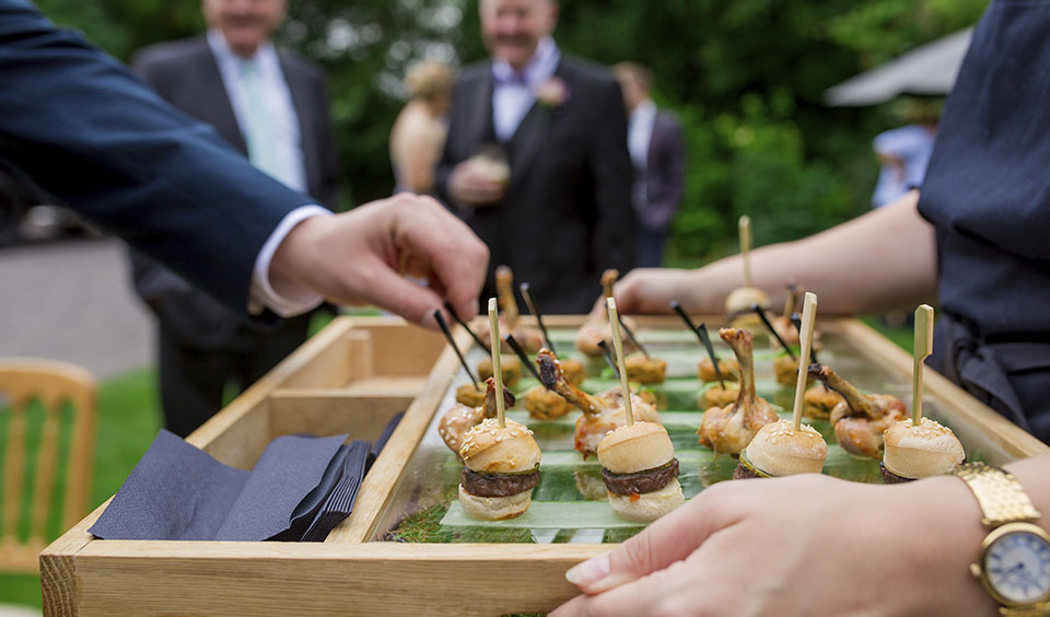 Guests enjoy delicious canapes after the wedding ceremony served by the expert on-site catering team