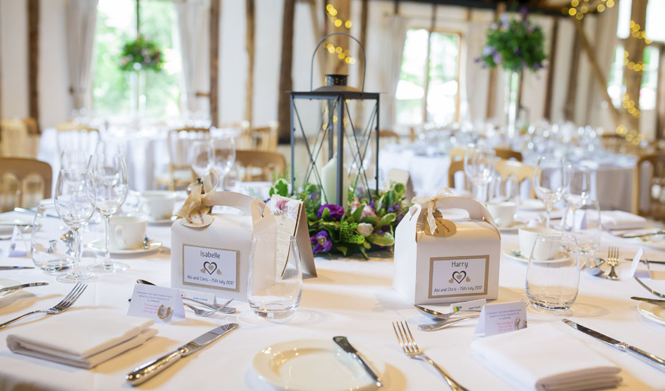 Lantern wedding centrepieces look beautiful as guests are given wedding favours in a white box