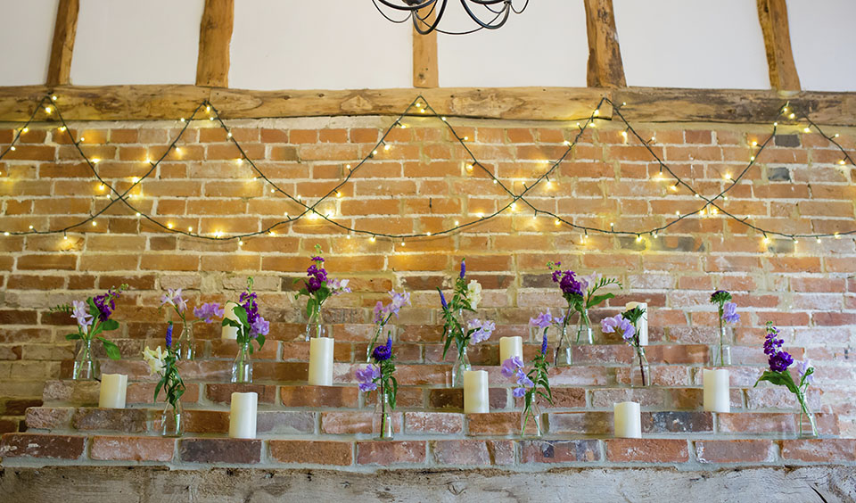 Twinkling fairylights are hung across the wall in the snug with jars or purple flowers above the fireplace