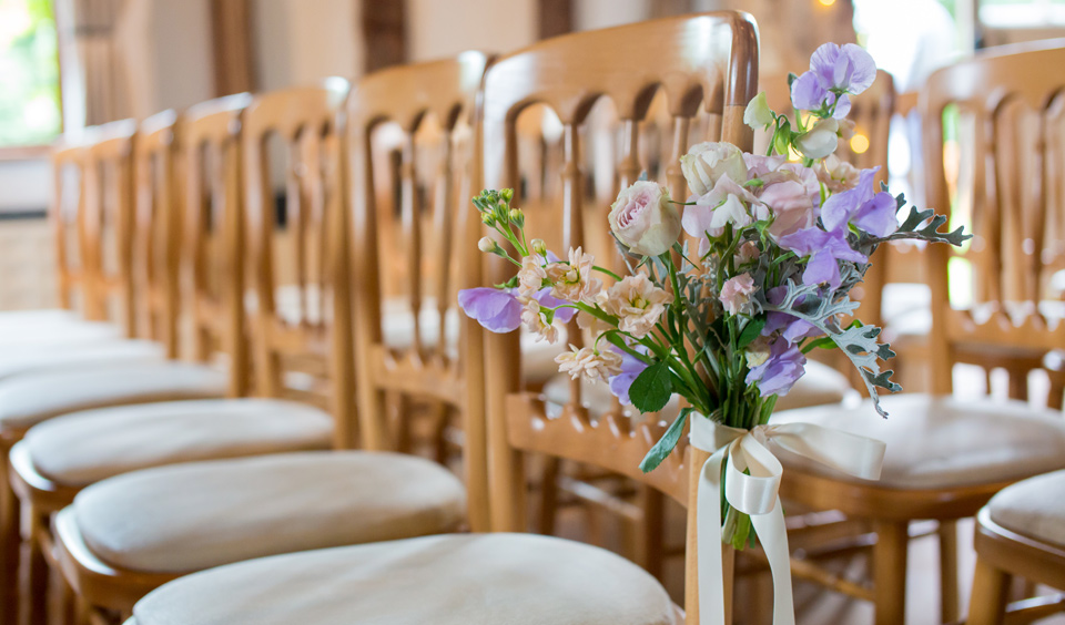 Delicate purple flowers are tied to the chairs for the wedding ceremony – rustic wedding ideas