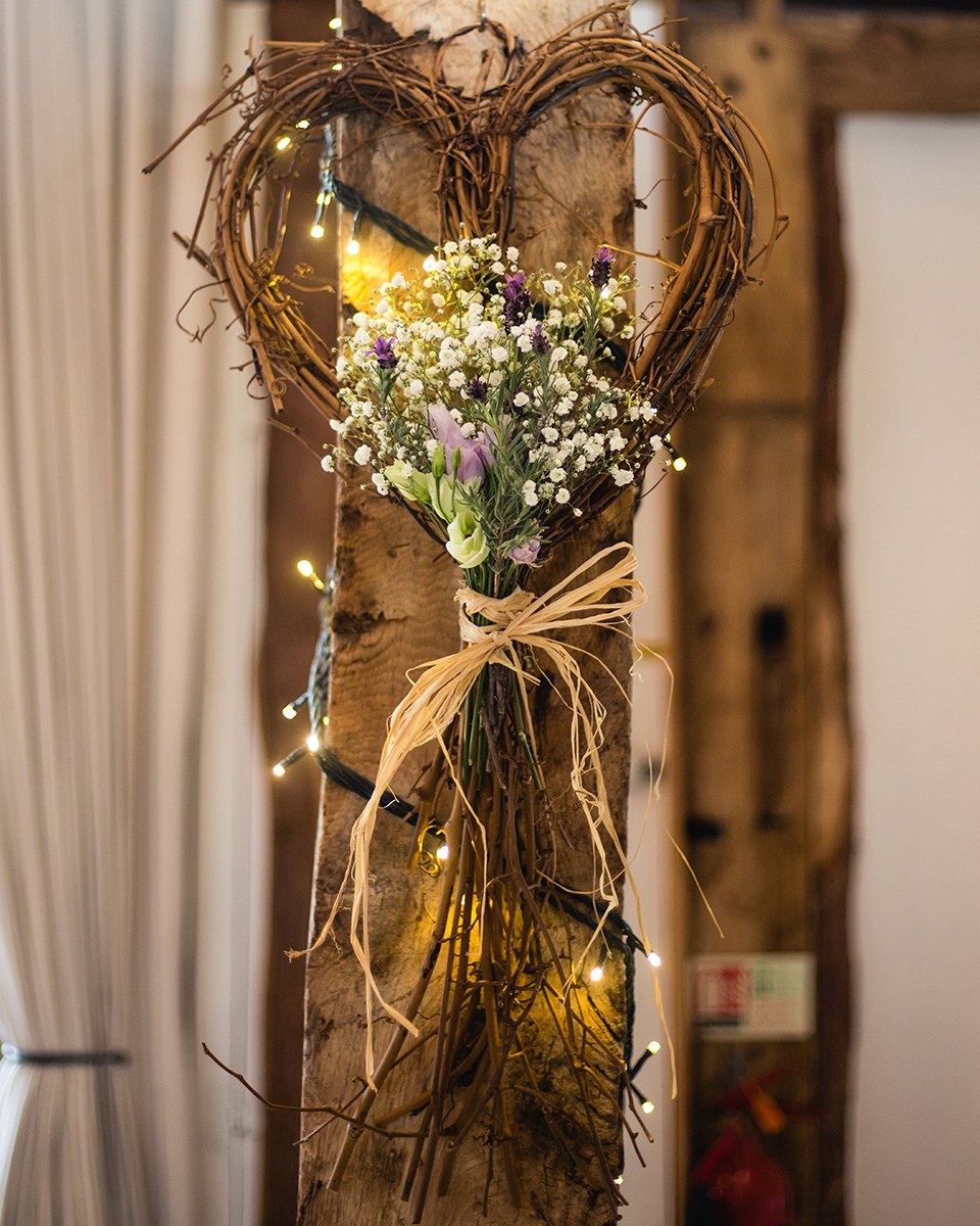 A heart shaped wooden decoration tied with purple flowers and gypsophila adorns the exposed wooden beams