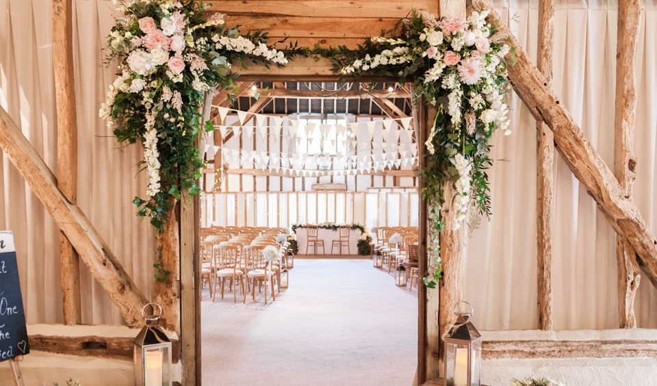 Add greenery to your wedding like this pretty flower arrangement that hangs over the ceremony barn door