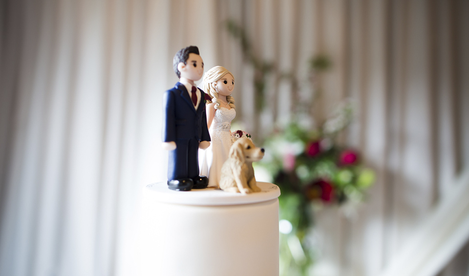 A wedding cake topper in the shape of the bride and groom adds a personal touch