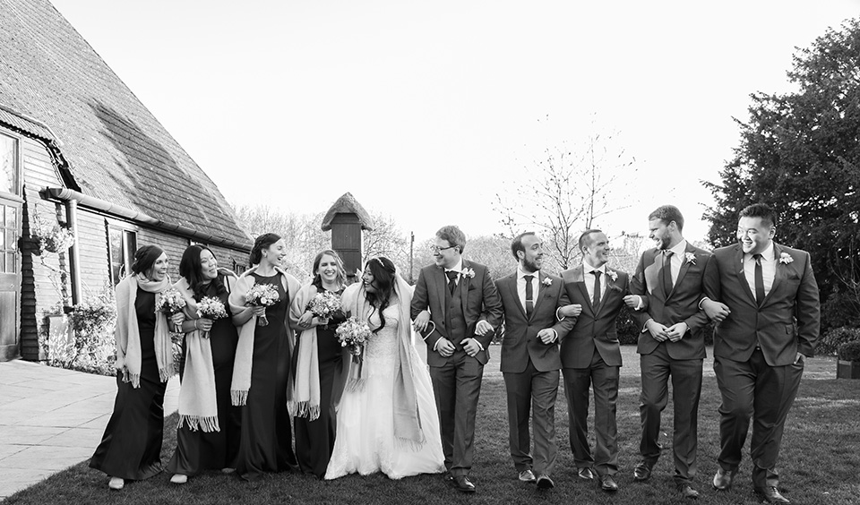 The bride and groom along with their bridesmaids and groomsmen enjoy Clock Barn's gardens