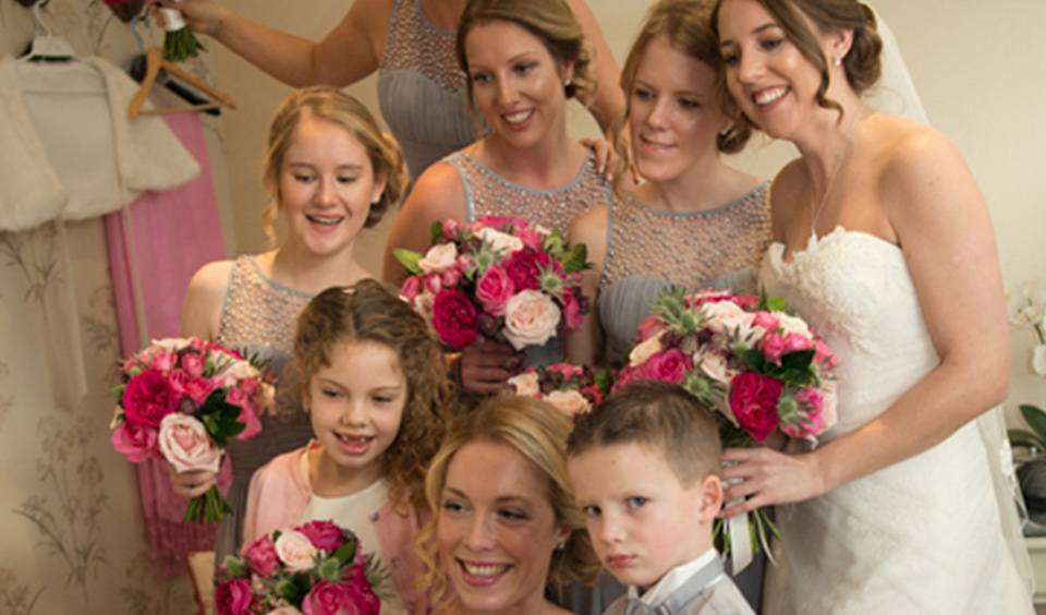 The bride and bridesmaids stand together for a photo holding their pink bouquets – wedding flowers