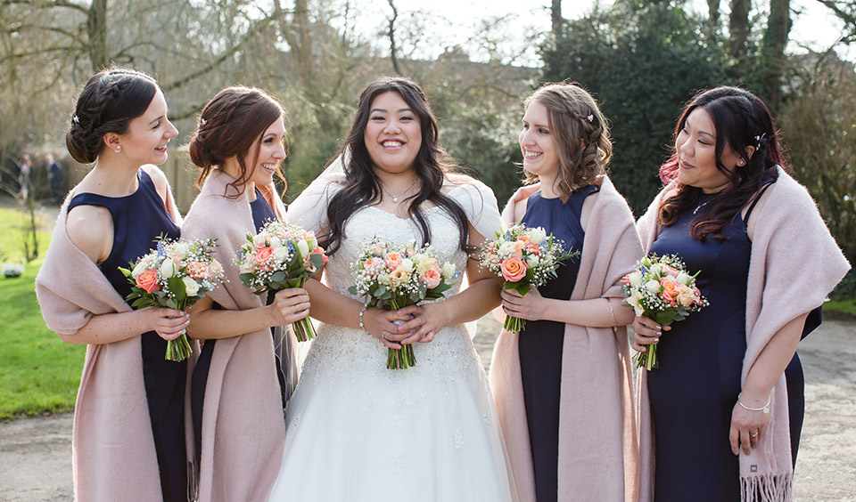 The bride stands with her bridesmaids each wearing navy blue bridesmaid dresses and pink shawls