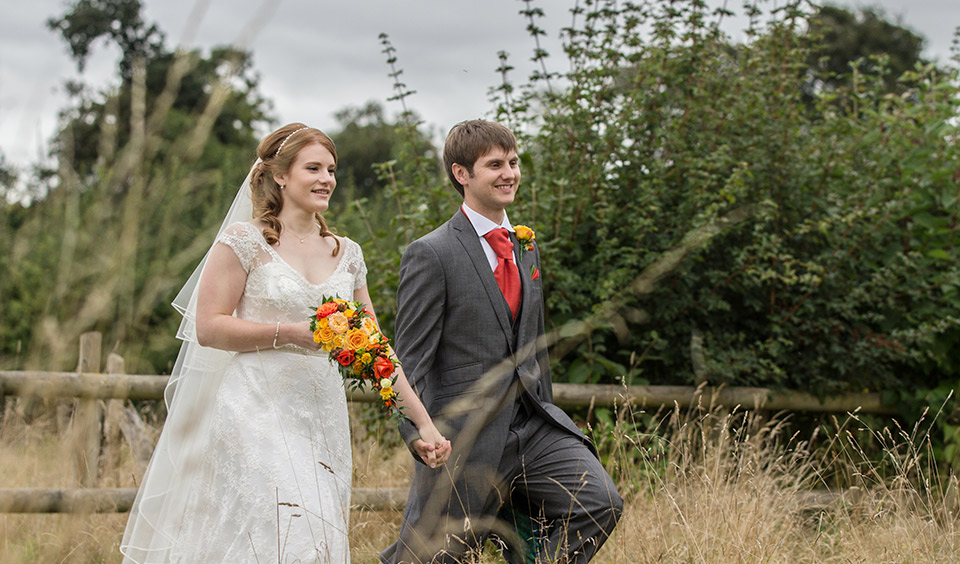The happy newlyweds take a stroll around the beautiful countryside setting at Clock Barn