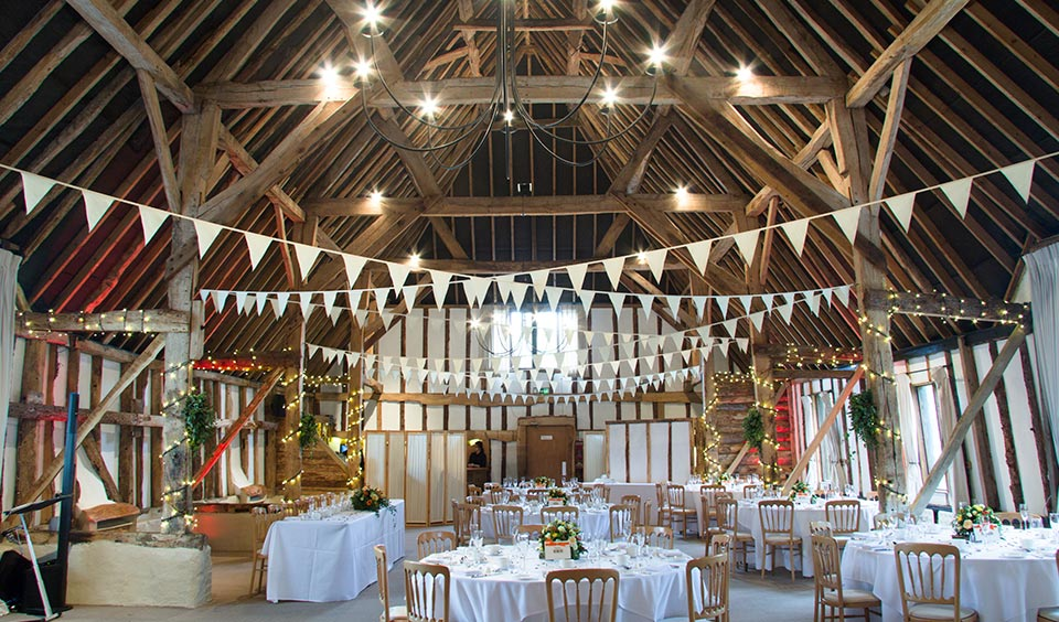 The rustic wedding barn with exposed oak beams looked beautiful set up for the wedding breakfast