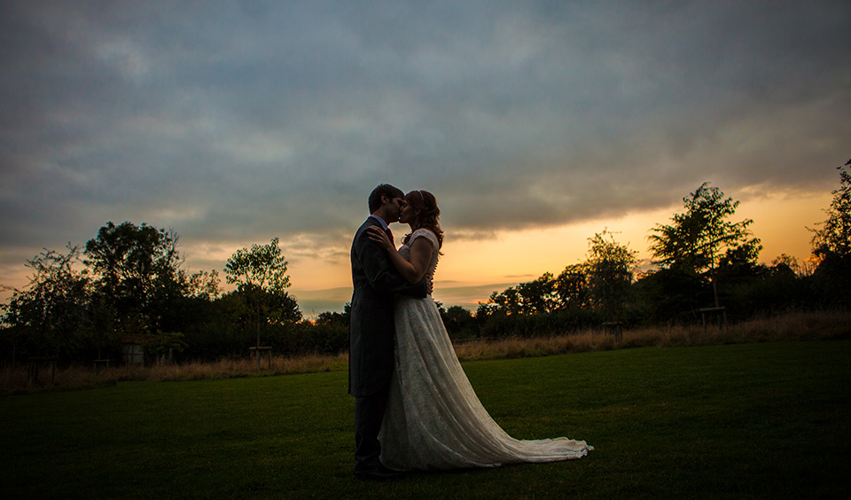 The couple embrace and share a kiss as the sun sets on their wedding day at Clock Barn