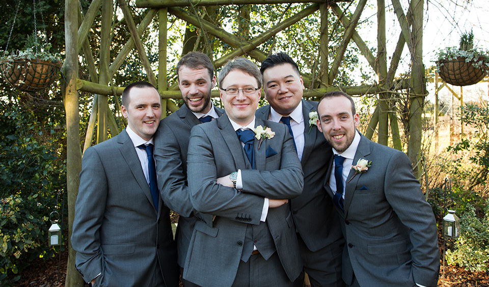 The groom and his groomsmen each wore a grey suit with navy blue ties and flower buttonholes