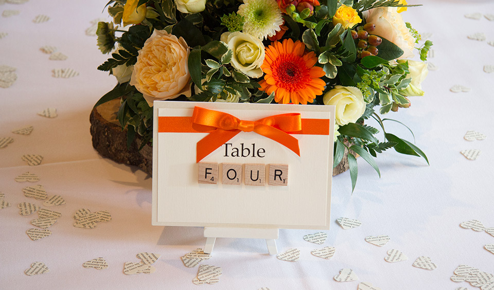 Each table number was spelt out using Scrabble tiles and decorated with an orange ribbon