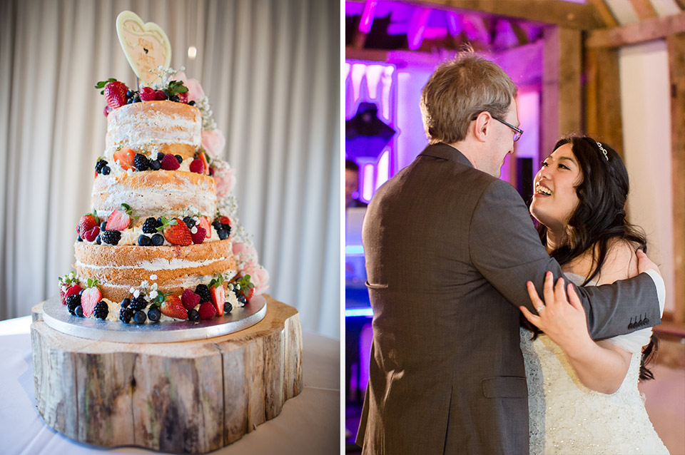 A three-tier naked wedding cake decorated with fruit stands on a tree stump as the couple enjoy their first dance