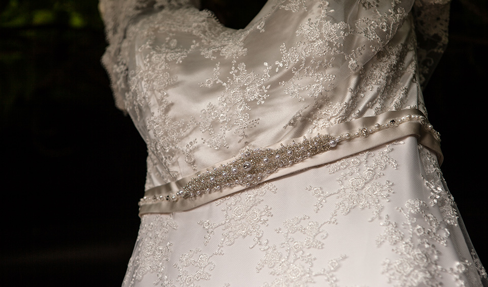 A close up of the bride's wedding dress with embellished satin belt and embroidered bodice