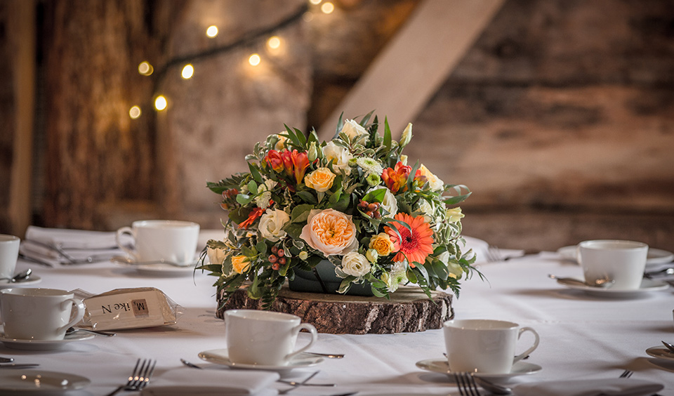 Gorgeous arrangements of wedding flowers in shades of orange peach and ivory adorned each table
