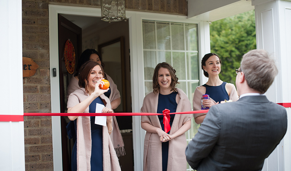 The groom, bride and bridesmaids enjoy traditional Chinese games the morning of the wedding