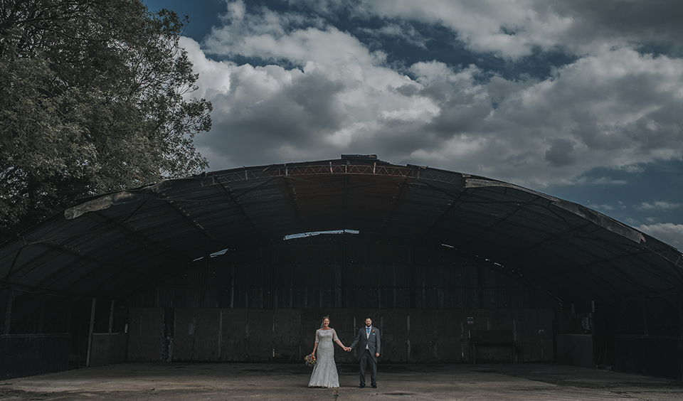 The bride and groom have a photo in a rustic disused barn at Clock Barn, Hampshire – wedding photos