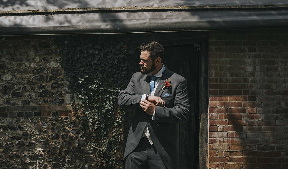 The groom wearing a grey suit takes a moment at Clock Barn Hampshire