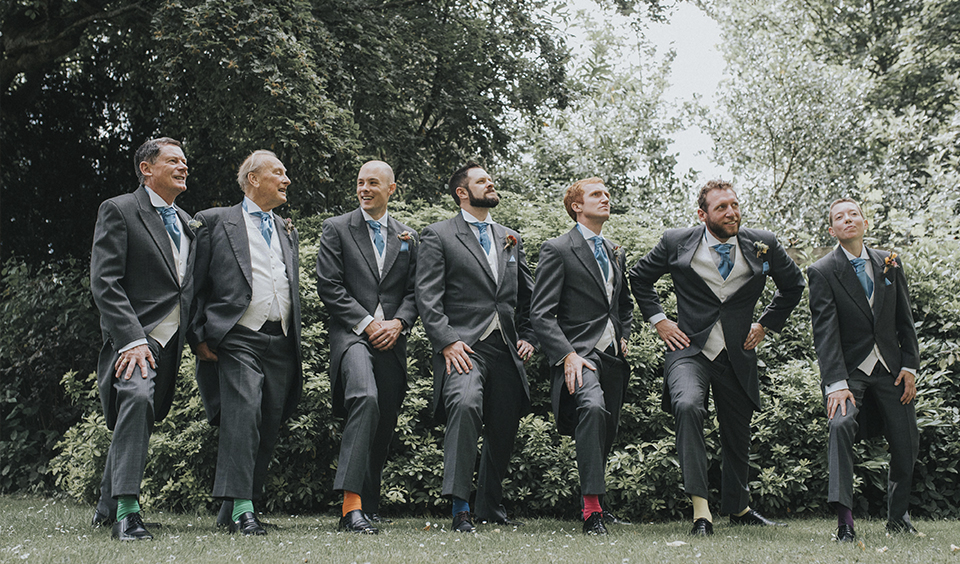 The groom and groomsmen share a fun moment in the gardens at Clock Barn Hampshire