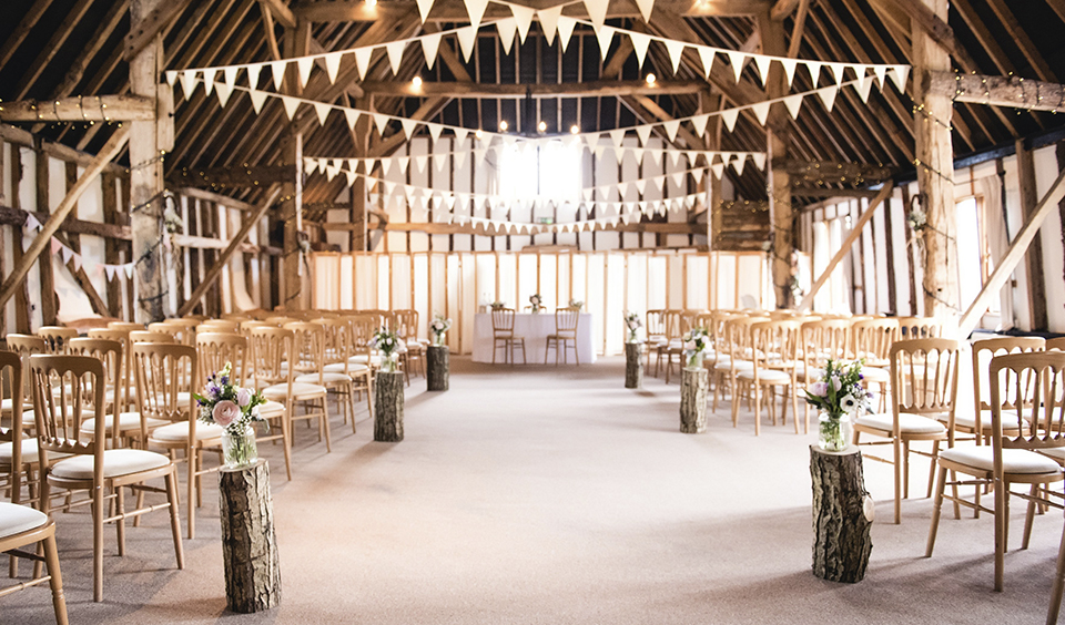 Decorate the aisle with bunting and jars of rustic flowers set on wood slices for an autumnal feel