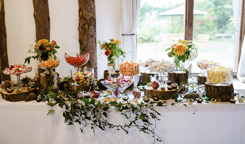 The sweet table adorned with seasonally coloured flowers and treats set on wood slices for a perfect autumnal look