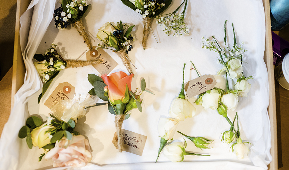 Delicate roses with sprays of baby's breath and sprigs of eucalyptus make beautiful button holes