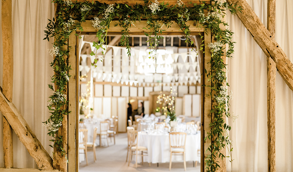 Floral arches of gypsophila beautifully frame the entrance the barn for a simple yet elegant look