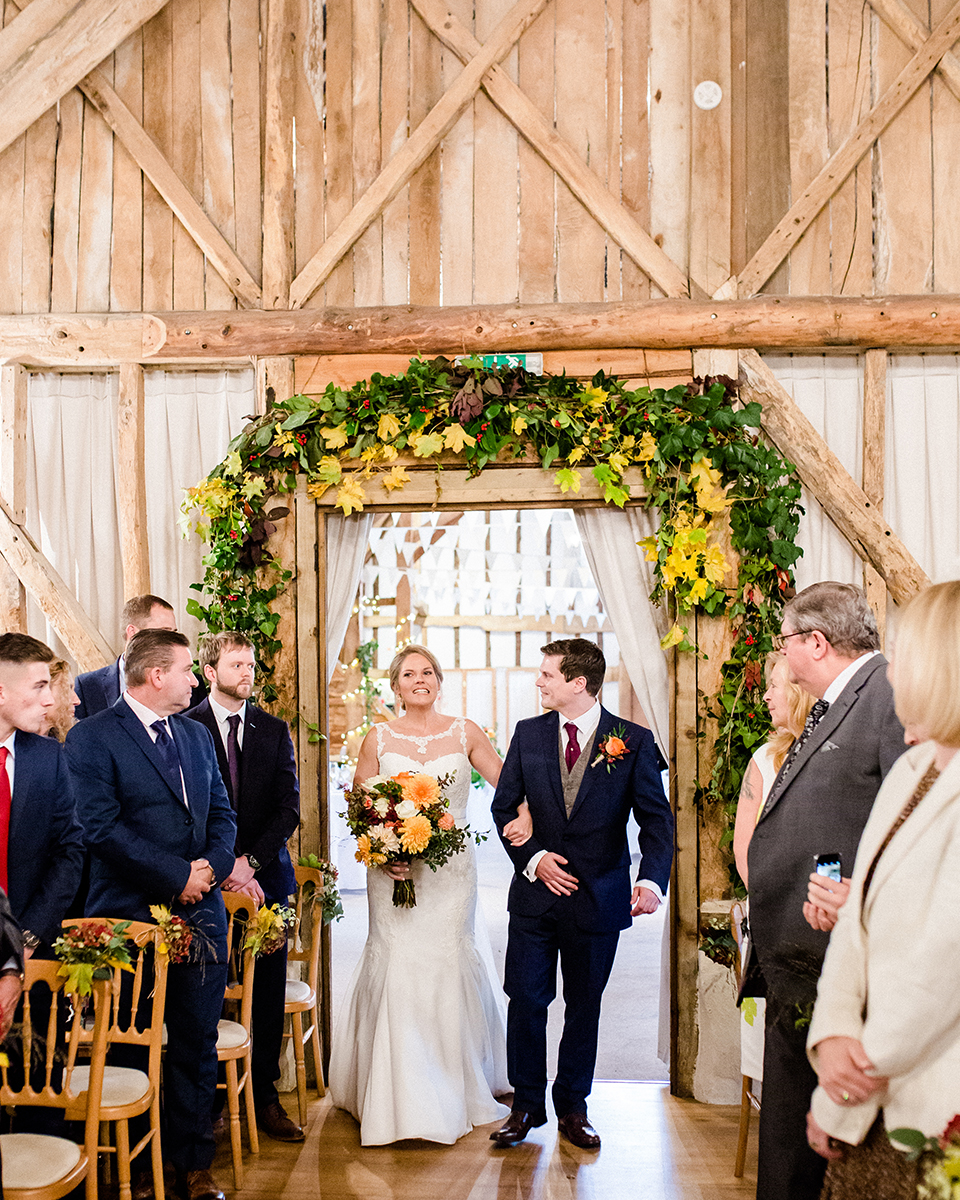 Decorate the barn with blooms of yellow and gold and lots of greenery to match the bridal bouquet
