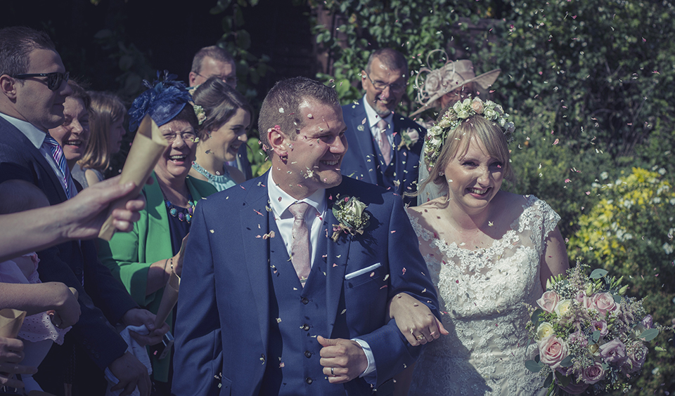 Wedding guests throw natural confetti over the happy newlyweds at this wedding at Clock Barn in Hampshire
