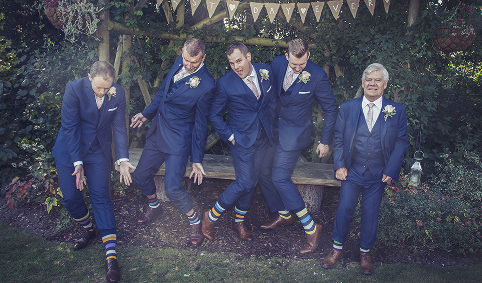 The groom and groomsmen wore navy wedding suits with blush pink ties, matching stripy socks and dark tan shoes