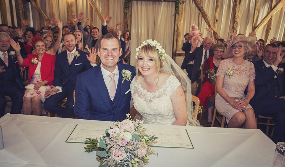 The happy couple pose for a photo after signing the register at Clock Barn Hampshire