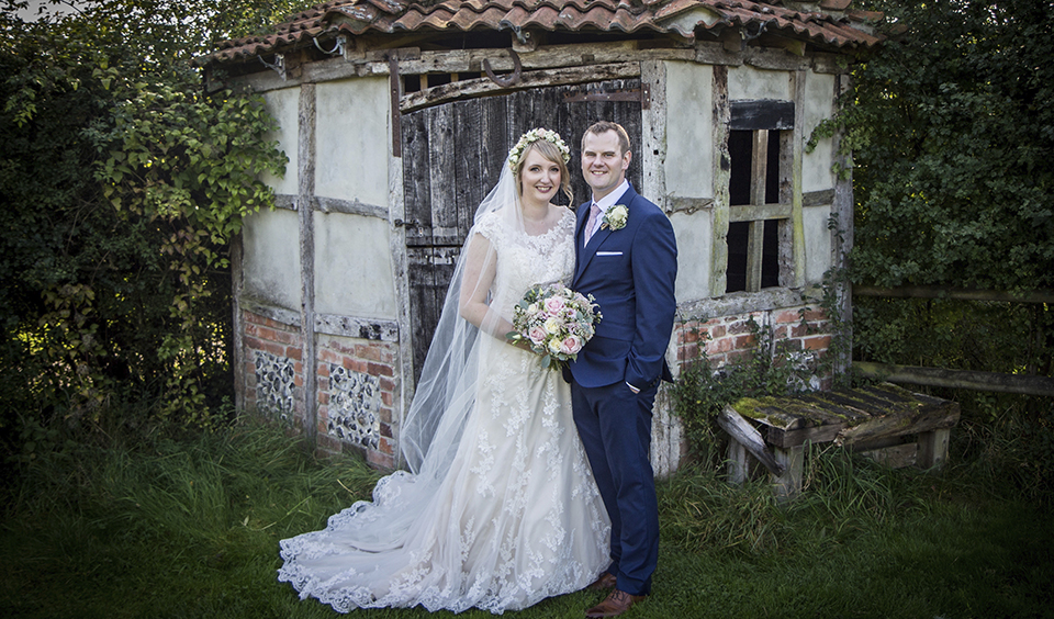 The bride and groom pose for a photo in the garden at Clock Barn in Hampshire