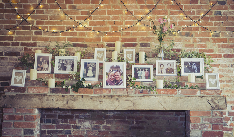 Pretty flowers and photos of the couple and their loved ones adorned the rustic fireplace at Clock Barn