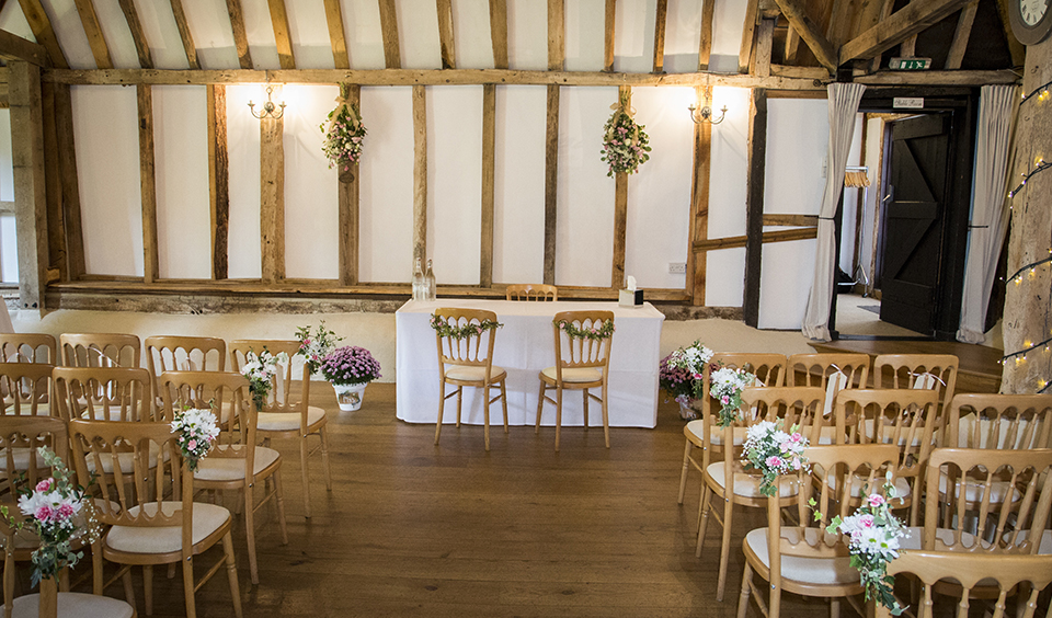 Pretty pink and white bouquets were used to decorate the barn for the ceremony at Clock Barn