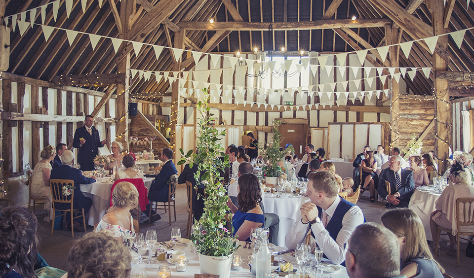 The wedding guests enjoy listening to the wedding speeches at this barn venue in Hampshire
