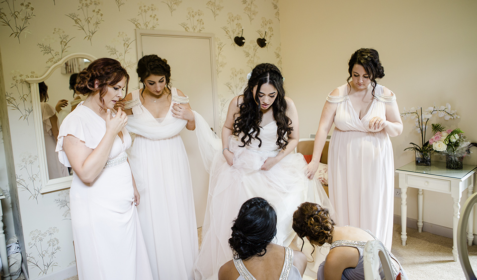 The bride and her bridesmaids make the final touches before wedding ceremony at Clock Barn in Hampshire