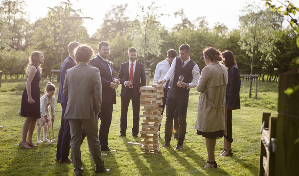 Wedding guests enjoy a game of Jenga in the gardens at this barn wedding in the South East of England