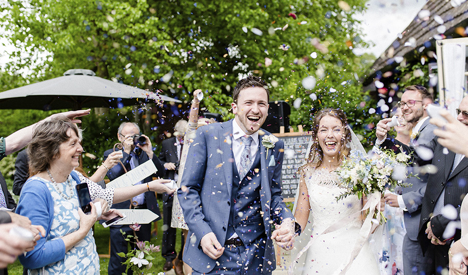 The happy newlyweds have confetti thrown over them at this barn wedding in Hampshire