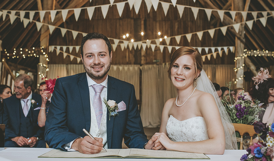 The happy newlyweds sign the register after the wedding ceremony at Clock Barn in Hampshire