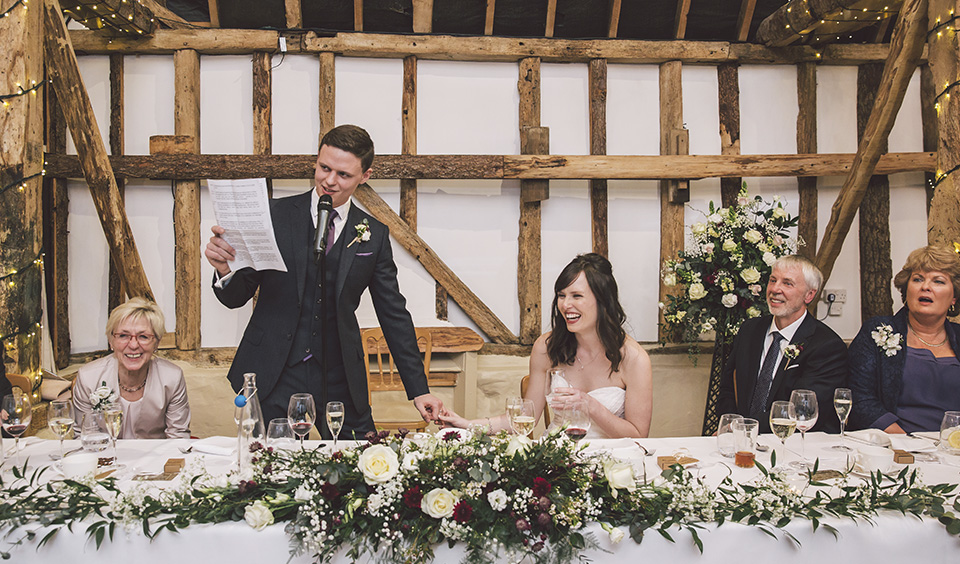 The bride and wedding guests enjoy the groom's speech at this barn wedding in rural Hampshire