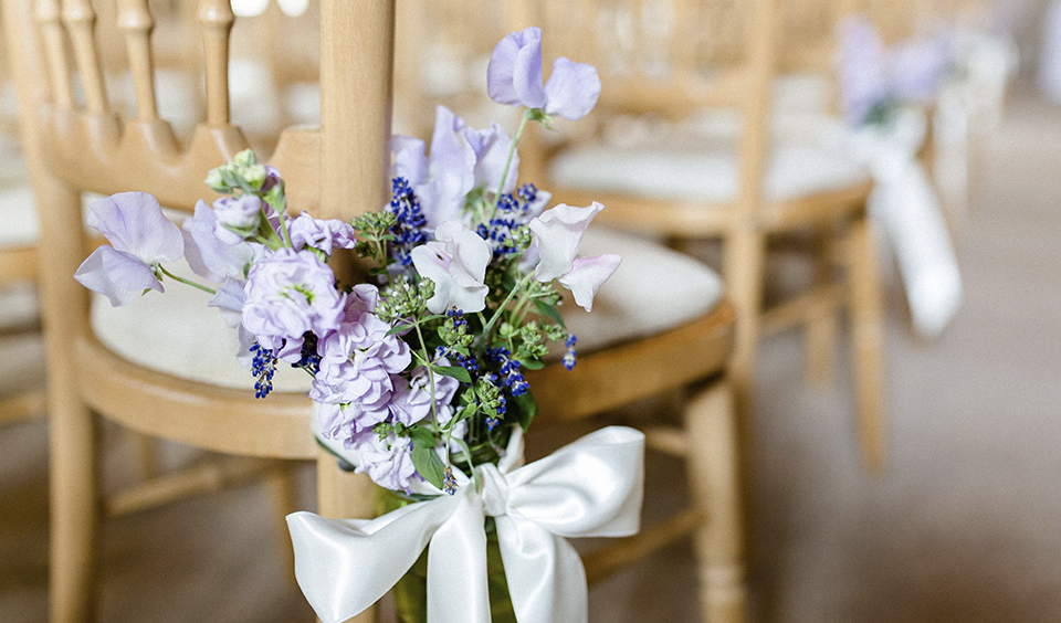 Decorate the chairs along your wedding aisle with seasonal flowers for your summer barn wedding in Hampshire